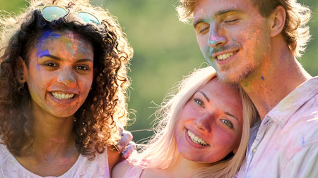 Positive emotions of happy male and female friends hugging at colour festival