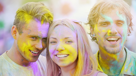Excited faces of beautiful young people covered in colors smiling at camera