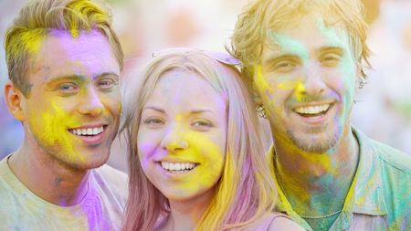 Smiling friends at color festival celebration, having fun on summer weekend