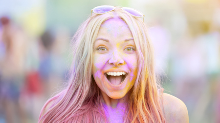 Excited young lady covered in Holi colors smiling camera, having fun at festival