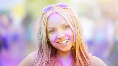 Happy young lady smiling to camera, having fun Holi festival, summer celebration