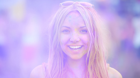 Sincere smile of cheerful young woman having fun at exciting color festival Stock Photo
