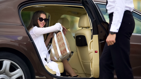 Private chauffeur opening door for beautiful female passenger, car services Banco de Imagens - 98190541