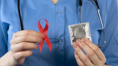 Doctor warning about AIDS disease showing red ribbon and condom, health campaign