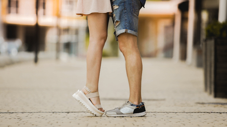 Feet of male and female close to each other, girl raising on tiptoes, dating