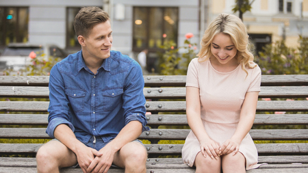 Shy blonde girl smiling, attractive guy flirting with beautiful woman on bench