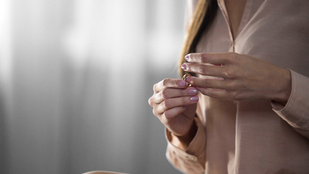 Woman taking her engagement ring off divorce, loneliness, relationship conflict