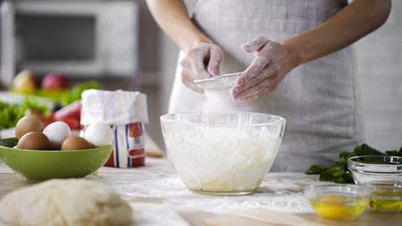 Woman hands sieving flour over glass bowl with dough, adding baking ingredients