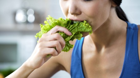 Wishing lose weight and be slim, lady making herself eating lettuce, nutrition Stock Photo