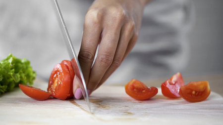 Housewife accidentally cutting her finger by knife in kitchen, home traumatism