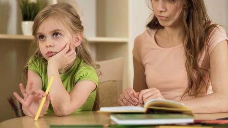 Little daughter ignoring mother making her to do homework, homeschooling Stock Photo