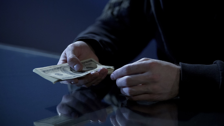 Male hands holding money, illegal payments, cash for contract killing closeup