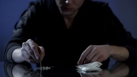 Young wealthy man forms cocaine lines on table, drug addiction among the rich
