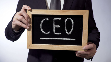 CEO written on blackboard, man in classic suit holding sign, business strategy