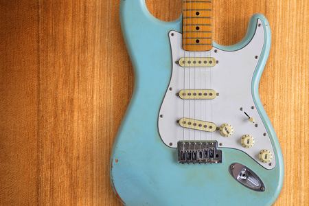 A light blue electric guitar in front of a warm-colored wooden panel 免版税图像