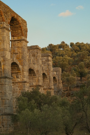Roman aqueduct or aquaduct in a ravine on the Greek island Lesbos. The ancient archways are hidden in an olive grove. photo