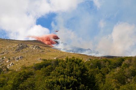 forest fire: Bombero atacante avi�n o el agua extingue el incendio forestal en una ladera de la monta�a.