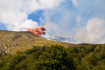 quell: Firefighter plane or water bomber extinguishes forest fire on a mountain slope. Stock Photo