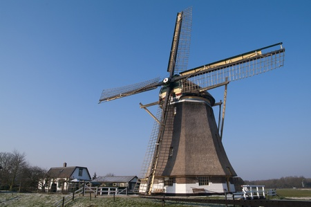 watermanagement: Dutch windmill in the winter on a green dike covered with hoarfrost.