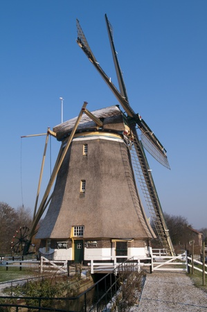 Dutch windmill in the winter on a green dike covered with hoarfrost. photo