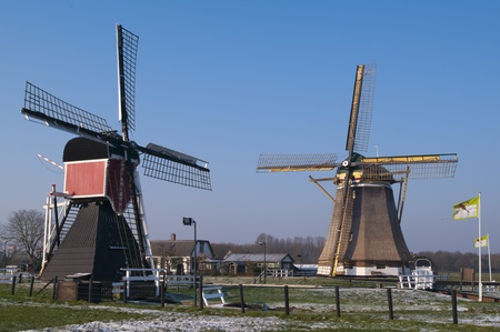 watermanagement: Two historic dutch windmills against a winter sky in a meadow covered with hoarfrost.