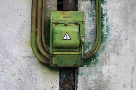 old green rusty metal switch on beton wall Stock Photo