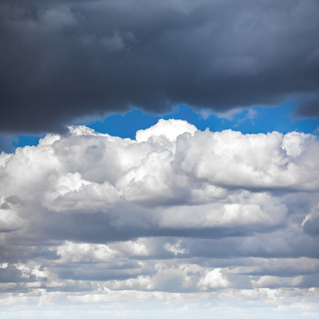 air: Blue sky and multiple heavy white clouds on spring noon. Nature background.
