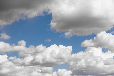 Blue sky and multiple heavy white clouds on spring noon. Nature background.