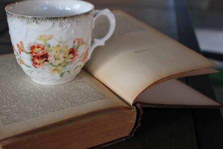 antigue tea cup on old book  Фото со стока