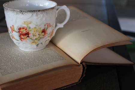 comfortable: antigue tea cup on old book  Stock Photo