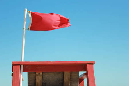 red flag at lifeguard stand at beach
