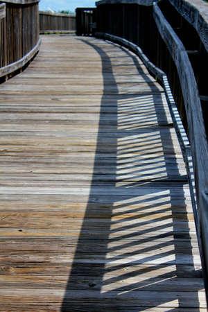 boardwalk to beach with railing shadow