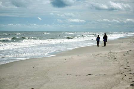 couple walking on beach in distance