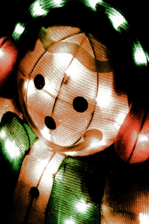 electric snowman lights up in the night