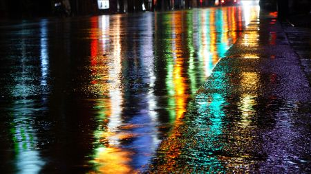 reflecting: Street neon lights reflected on a wet street in Tokyo