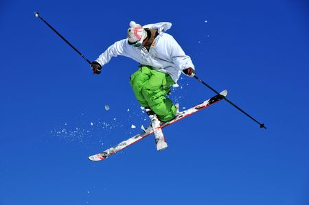 facing backwards: skier in green and white clothes performing a tele-heli with skis crossed at the same time as executing a full spin (in this shot, facing backwards) Stock Photo