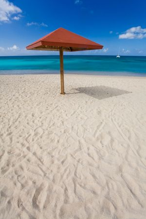 Shelters on white sand beach by turquoise waters on tropical island