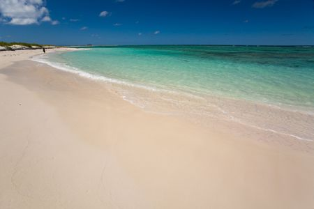 White sand beach and turquoise waters on tropical island