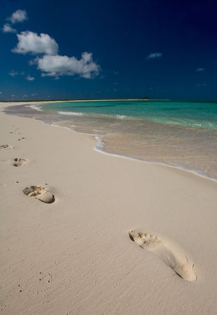 pristine corals: Footprints on white sand beach near turquoise waters on tropical island