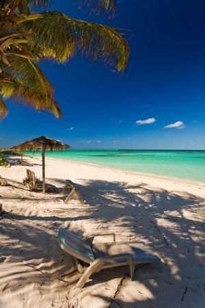 Chairs and shelters on tropical white sand beach by turquoise waters