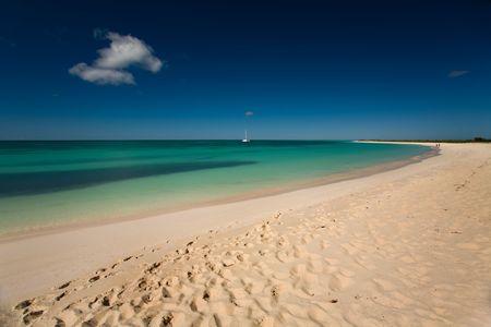 pristine coral reef: Barca su acque turchesi visto dalla spiaggia di sabbia bianca di un'isola tropicale