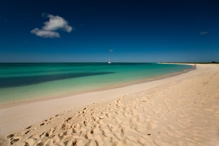 remoteness: Boat on turquoise waters seen from the white sand beach of a tropical island