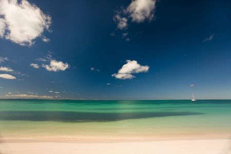 pristine corals: Boat on turquoise waters seen from the white sand beach of a tropical island