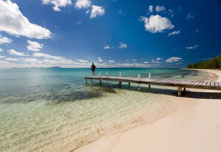 pristine corals: Young woman standing on dock beside a tropical white sand beach and turquoise waters