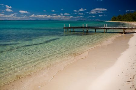 Dock beside a tropical white sand beach and turquoise waters photo