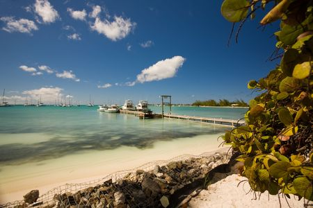 remoteness: Dock and boats beside a tropical white sand beach and turquoise waters