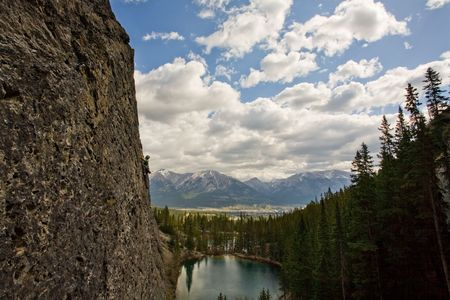 Rock climber high above lake in the Canadian Rockies