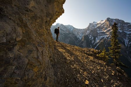 Silhouette of young man exploring the Canadian Rocky Mountains in the Spring