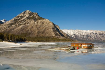 Log cabin on icy lake in the Canadian Rockies