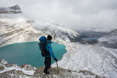 Young man stands high above alpine lake in the Rocky Mountains, Banff National Park, Alberta, Canada.